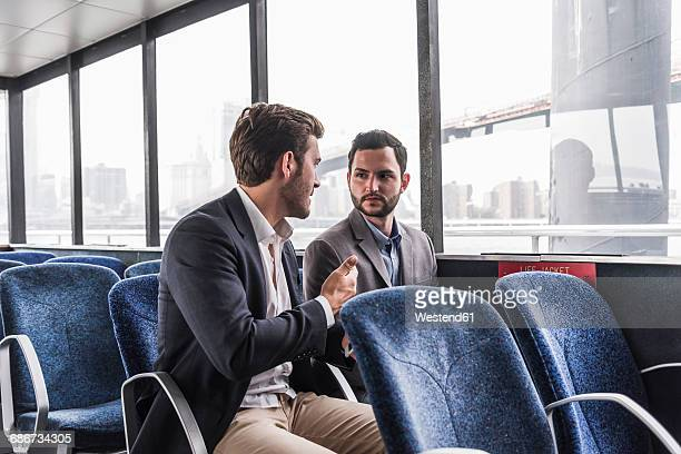 Two businessmen talking on passenger deck of a ferry