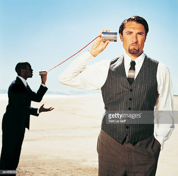 Two businessmen talking on tin can phone