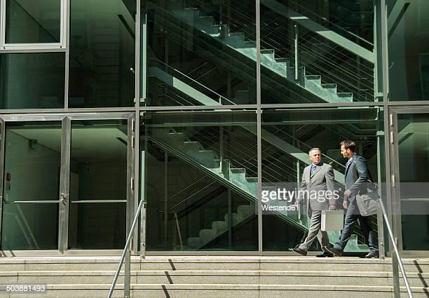 Two businessmen talking outside office building