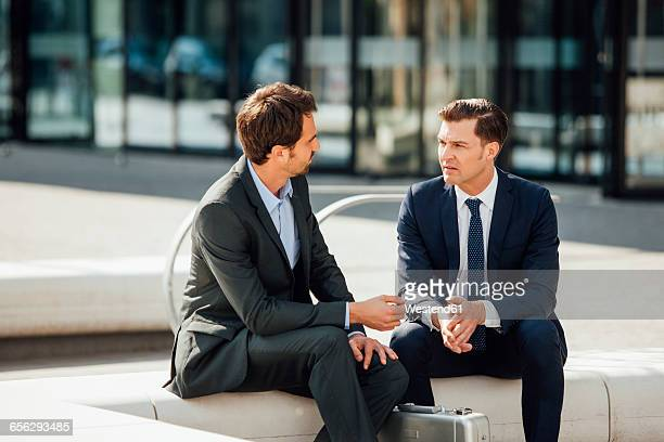 Two businessmen talking outside office building