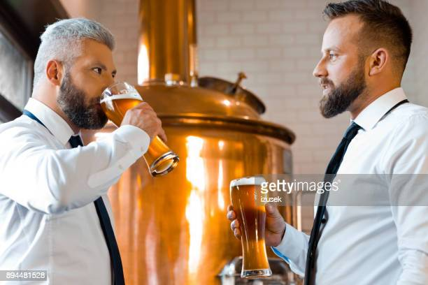 two businessmen talking over beer in the microbrewery - tasting stock pictures, royalty-free photos & images