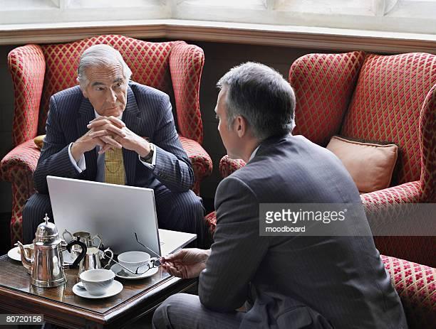 two businessmen talking - zurücklehnen stock-fotos und bilder
