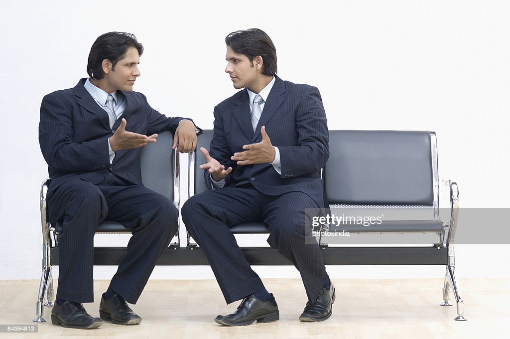 two businessmen talking to each other ストックフォト getty images