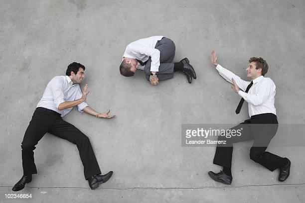 Two businessmen throwing a third around