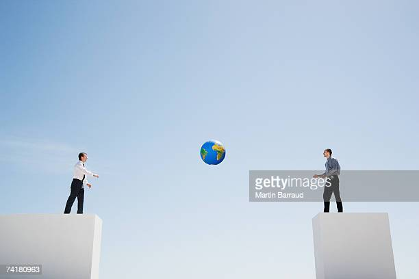 two businessmen tossing standing on walls with large gap tossing globe - man with big balls stock photos and pictures