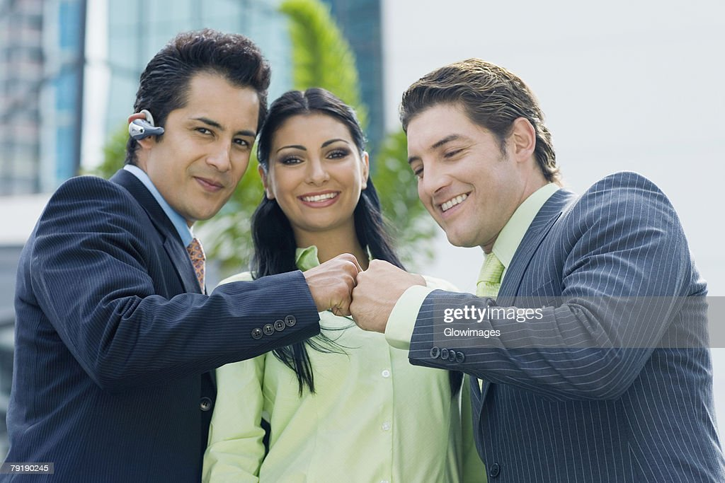 Two businessmen touching knuckles and a businesswoman smiling : Stock Photo