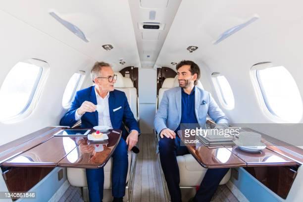 dos hombres de negocios que viajan en jet corporativo - izusek fotografías e imágenes de stock