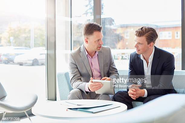 Two businessmen using digital table at office meeting