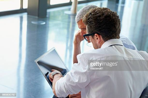 Two businessmen using laptop in office lobby
