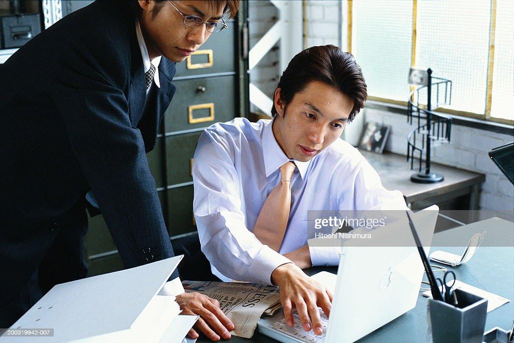 Two businessmen using laptop : Stock Photo