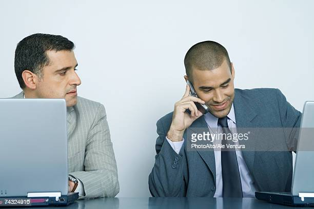 Two businessmen using laptops, one using cell phone while other watches him