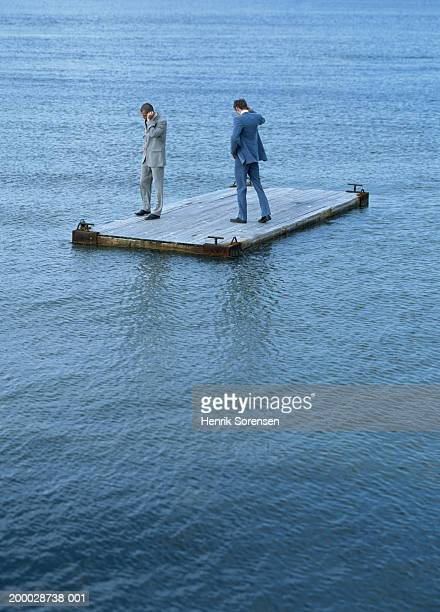 Two businessmen using mobile phones on raft at sea