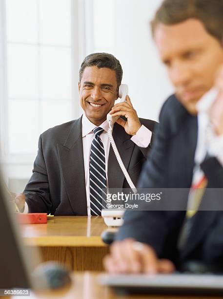 two businessmen using telephones