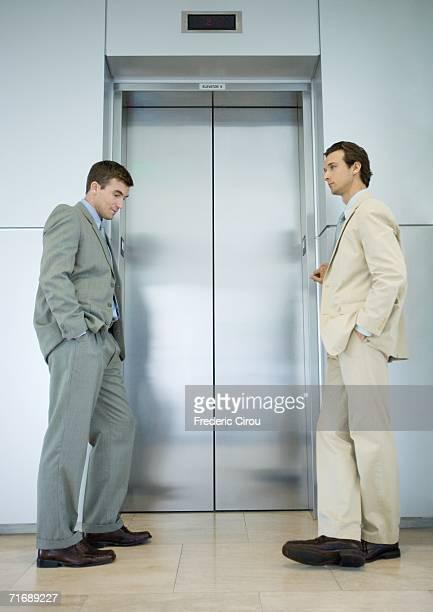 two businessmen waiting by elevator door - metallic suit stock photos and pictures