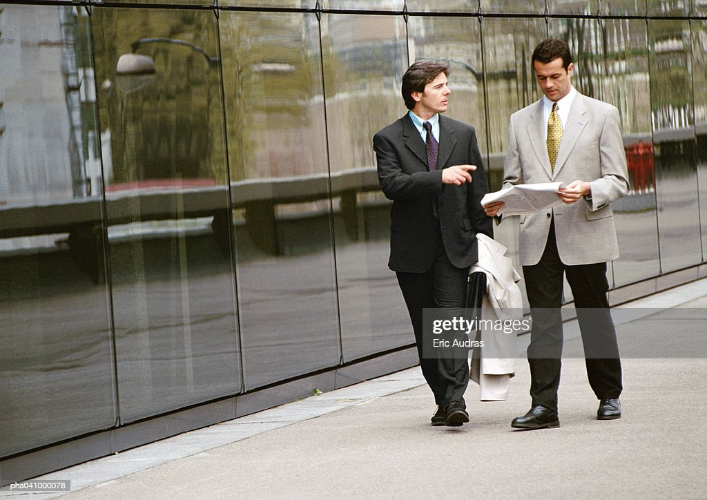 Two businessmen walking along sidewalk in front of building : Stockfoto