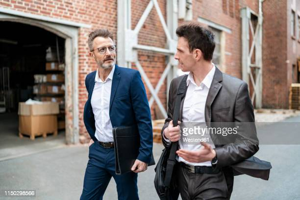 two businessmen walking and talking at an old brick building - two people stock-fotos und bilder
