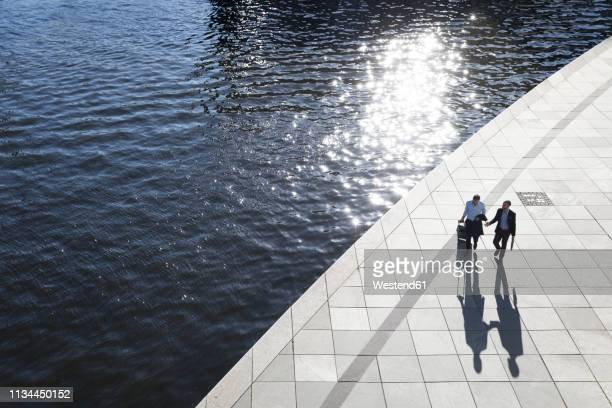 two businessmen walking and talking at the riverbank - hauptstadt stock-fotos und bilder