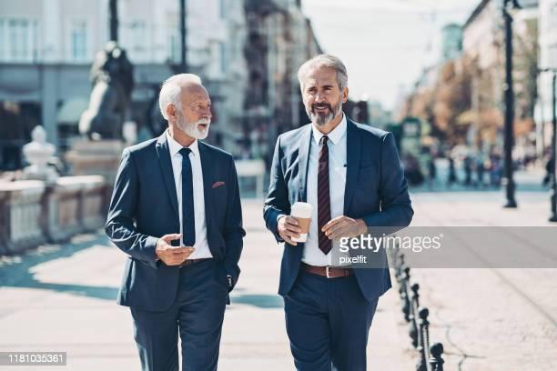 2人のビジネスマンが屋外を歩いて話す - エグゼクティブディレクター ストックフォトと画像
