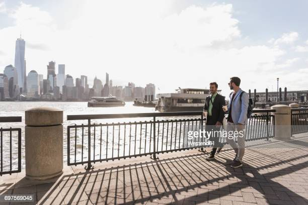 USA, two businessmen walking at New Jersey waterfront with view to Manhattan