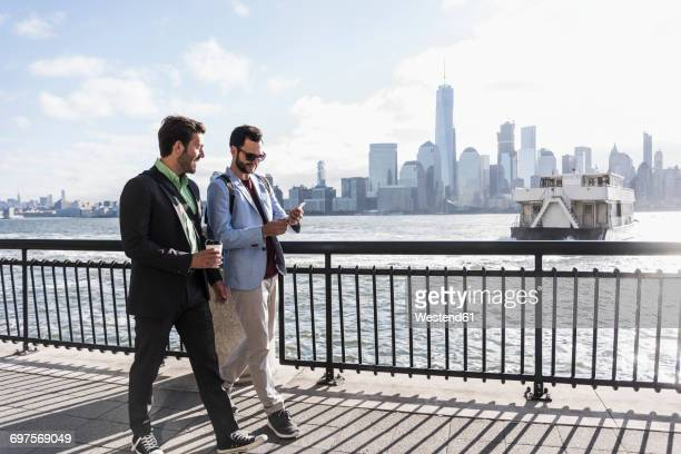 usa, two businessmen walking at new jersey waterfront with view to manhattan - gemeinsam gehen stock-fotos und bilder