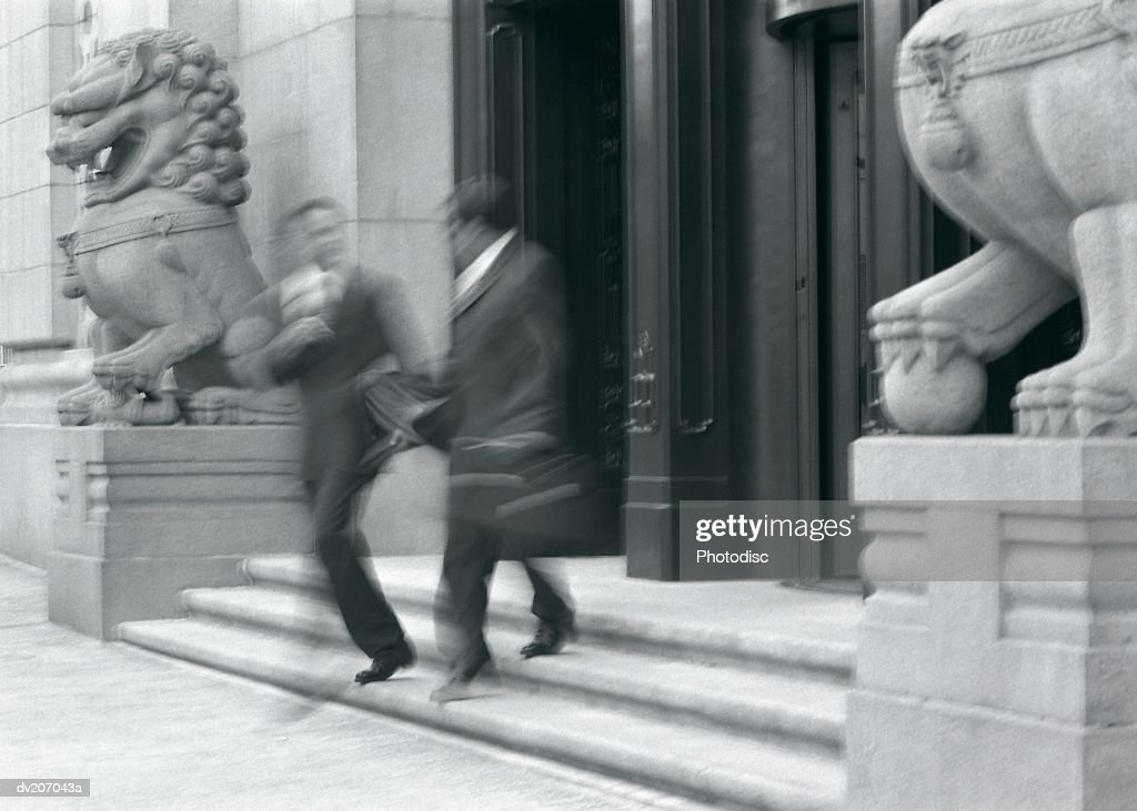 Two businessmen walking down stairs : Stock Photo