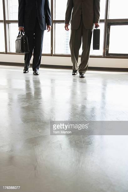 Deux hommes d'affaires marchant dans le couloir de grandes fenêtres