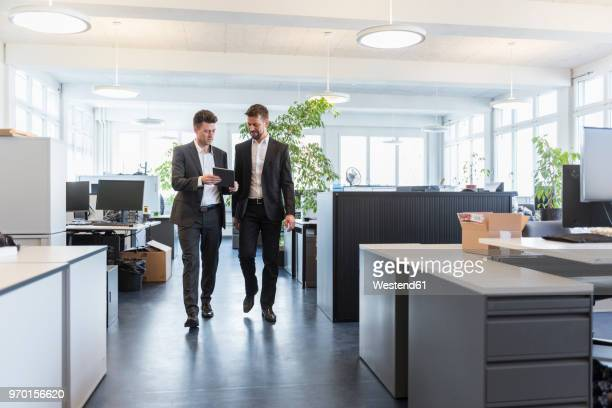 two businessmen walking in office, using digital tablet, talking - central europe stock photos and pictures