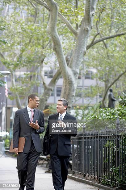 Two businessmen walking in street, talking
