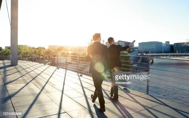 two businessmen walking on a bridge in the city - planung stock-fotos und bilder