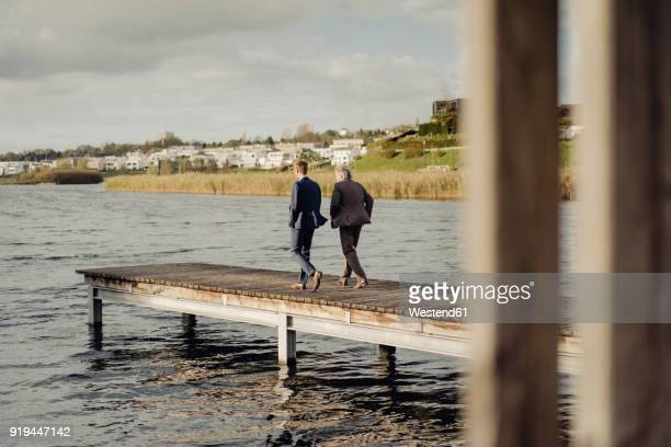 two businessmen walking on jetty at a lake - 後任 ストックフォトと画像