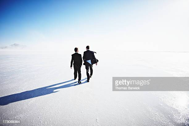 two businessmen walking on salt flats rear view - the hobbit: an unexpected journey stock pictures, royalty-free photos & images