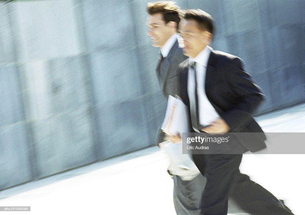 Two businessmen walking outdoors, blurred motion : Stockfoto