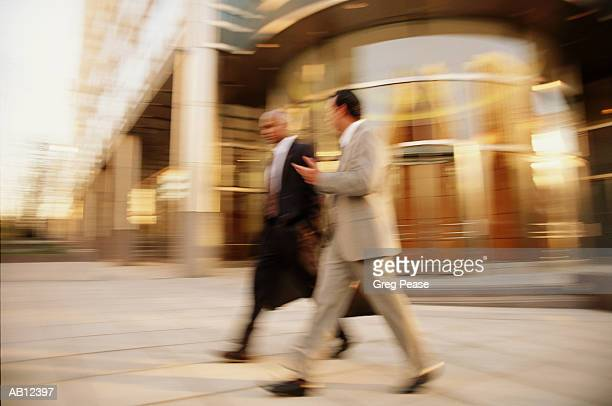 """two businessmen walking outdoors (blurred motion, distorted) - """"greg pease"""" stock pictures, royalty-free photos & images"""