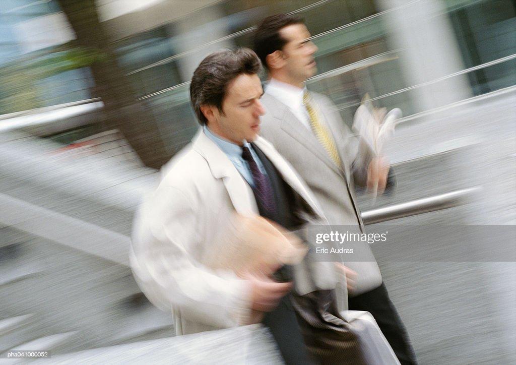 Two businessmen walking outside, blurred motion : Stockfoto
