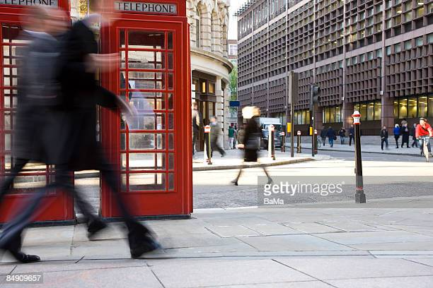 two businessmen walking past phone both - incidental people stock pictures, royalty-free photos & images