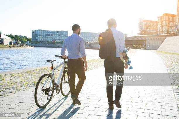 two businessmen walking with bicycle and skateboard at the riverbank - gemeinsam gehen stock-fotos und bilder
