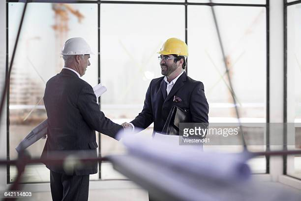 Two businessmen wearing hard hats shaking hands on construction site