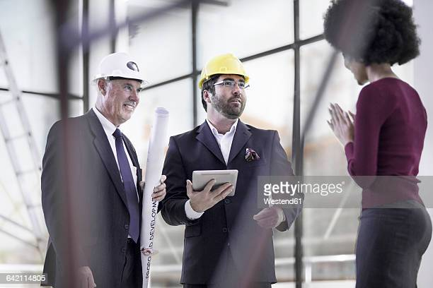 Two businessmen wearing hard hats talking to woman
