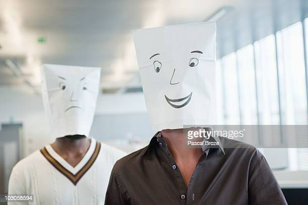 Two businessmen wearing paper bags of happy and sad faces