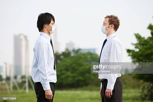 two businessmen wearing pollution masks, face to face - respirator mask stock pictures, royalty-free photos & images