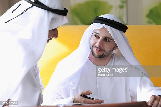 two businessmen wearing traditional clothing having meeting - hugh sitton stock pictures, royalty-free photos & images