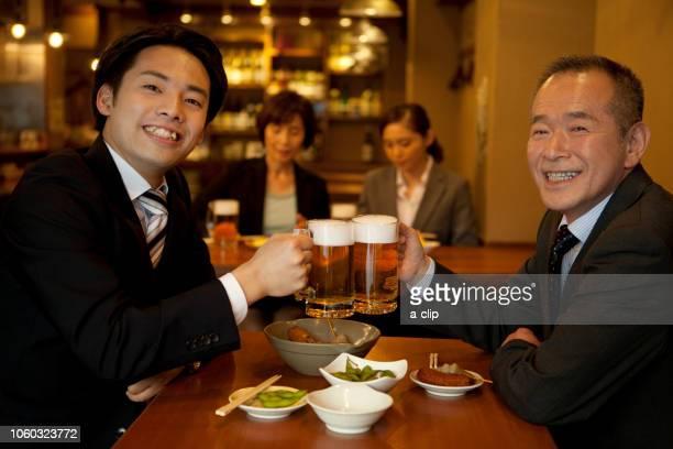 ビールで乾杯するビジネスマン2人 - evening meal ストックフォトと画像