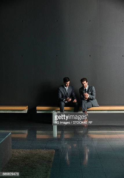 Two businessmen with cell phones on bench