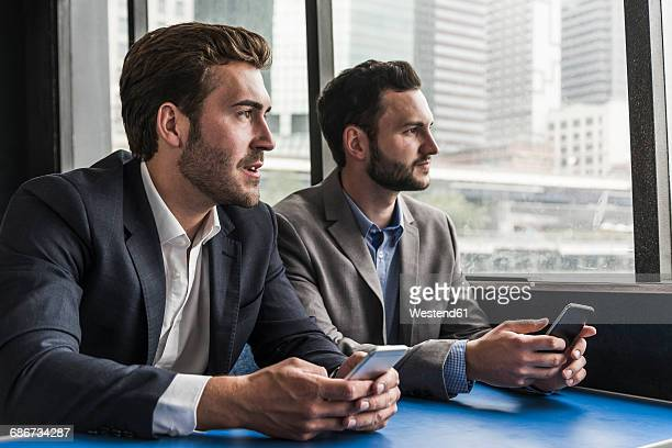 Two businessmen with cell phones on passenger deck of a ferry