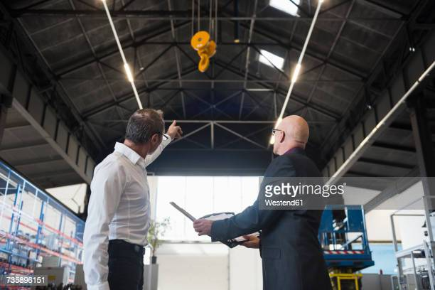 Two businessmen with clipboard on factory shop floor with bridge crane