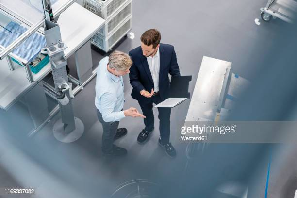 two businessmen with clipboard talking in a factory - finanzen und wirtschaft stock-fotos und bilder