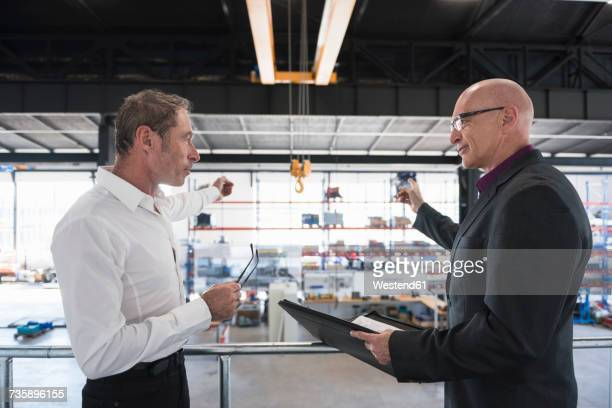 Two businessmen with clipboard talking on factory shop floor