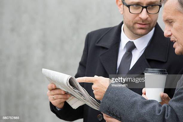 Two businessmen with coffee to go and newspaper