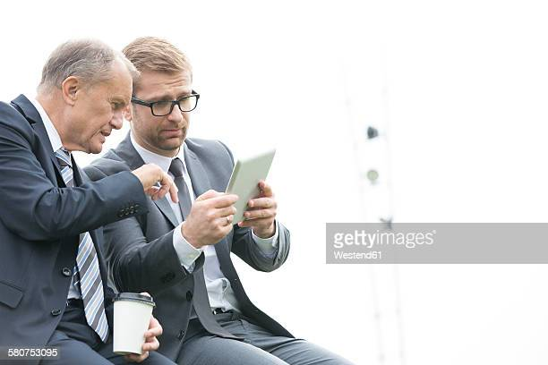 Two businessmen with digital tablet and coffee to go outdoors