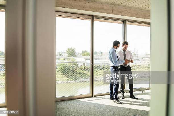 two businessmen with digital tablet at the window - formelle geschäftskleidung stock-fotos und bilder